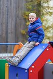 Cute school boy having fun outdoors at playground Royalty Free Stock Image