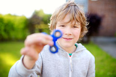 Cute school boy playing with fidget spinner on the playground. Popular stress-relieving toy for school kids and adults. Cute school boy playing with colorful stock photos