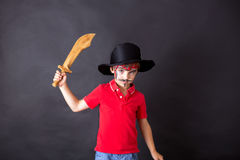 Cute school boy, playing games, painted as pirate, holding sword. Images on black background Stock Photo