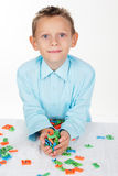 Cute school boy is playing with plastic letters Stock Photography