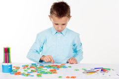 Cute school boy is playing with plastic letters Stock Photo