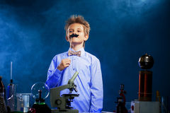 Cute school boy posing with fake mustache in lab Royalty Free Stock Photos