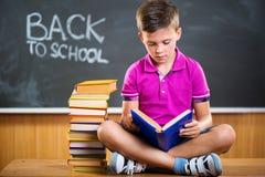 Cute school boy reading book in classroom. Against blackboard Royalty Free Stock Photography