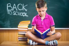 Cute school boy reading book in classroom. Against blackboard Royalty Free Stock Image
