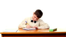 Cute school boy sitting, thinking and writing stock video
