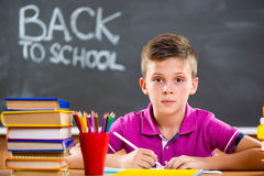 Cute school boy studying in classroom Stock Photography