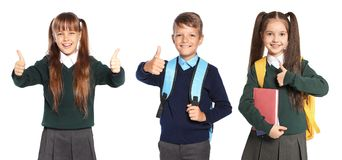Cute school children in uniform with backpacks. On white background stock photography