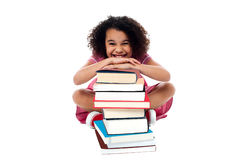 Cute school girl leaning over stack of books Stock Photo