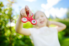 Cute school girl playing with fidget spinner on the playground. Popular stress-relieving toy for school kids and adults. Cute school girl playing with colorful stock photos