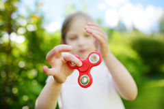 Cute school girl playing with fidget spinner on the playground. Popular stress-relieving toy for school kids and adults. Cute school girl playing with colorful royalty free stock image