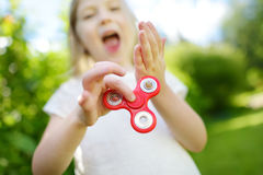 Cute school girl playing with fidget spinner on the playground. Popular stress-relieving toy for school kids and adults. Cute school girl playing with colorful royalty free stock photo