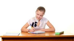 Cute school girl sitting, thinking and writing stock video
