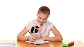 Cute school girl sitting, thinking and writing stock footage