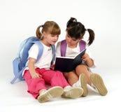 Cute school girls. Looking in notebook Royalty Free Stock Images