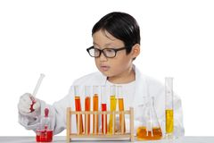 Cute schoolboy doing experiment on studio. Cute schoolboy working with chemical liquid while doing experiment in the studio, isolated on white background Royalty Free Stock Photo