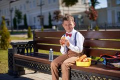 Cute schoolboy eating outdoors the school. Healthy school breakfast for child. Food for lunch, lunchboxes with sandwiches, fruits royalty free stock images