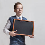 Cute schoolboy with empty chalkboard Stock Images