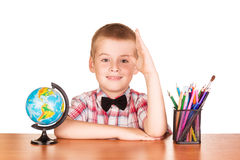 Cute schoolboy at his desk, globe and pencils  . Stock Image