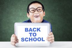 Cute schoolboy holding text of back to school. Cute schoolboy holding a digital tablet with text of back to school on the  while sitting in the classroom Royalty Free Stock Photos