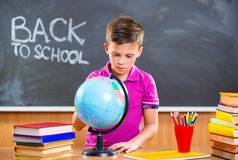 Cute schoolboy looking on globe Royalty Free Stock Photo
