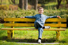 Cute schoolboy in a park Royalty Free Stock Photos