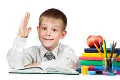 Cute schoolboy is pulling his hand to answer Royalty Free Stock Photography