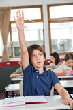 Cute Schoolboy Raising Hand In Classroom. Portrait of cute schoolboy raising hand while studying at desk in classroom Stock Image