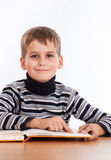 Cute schoolboy is reading a book Royalty Free Stock Photography