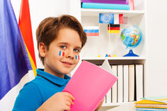 Cute schoolboy reading a book sitting at the desk Stock Photography