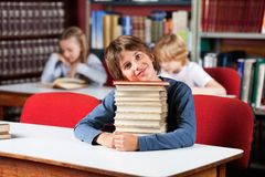Cute Schoolboy Sitting With On Stack Of Books At. Portrait of cute little schoolboy sitting with stack of books at table in library and classmates in background Stock Photos