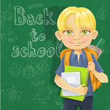 Schoolboy with textbooks and backpack near blackbo Royalty Free Stock Photos
