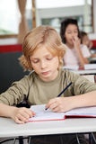 Cute Schoolboy Writing In Book At Desk Royalty Free Stock Photos
