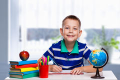 Cute schoolboy is writing in classroom Royalty Free Stock Photo