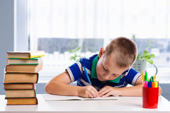 Cute schoolboy is writing  on a white background Stock Image
