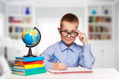 Cute schoolboy is writting isolated on a white background Stock Image