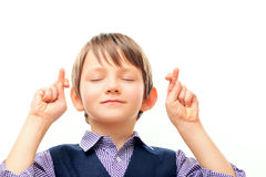 Cute schoolchild in keeping fingers crossed Royalty Free Stock Images
