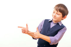 Cute schoolchild in suit with imagined gun Stock Photography