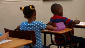 Cute schoolchildren in the classroom stock video