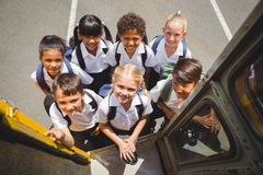 Cute schoolchildren getting on school bus Royalty Free Stock Photo