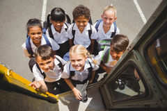 Cute schoolchildren getting on school bus Stock Photography