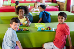 Cute schoolchildren having meal Royalty Free Stock Photography