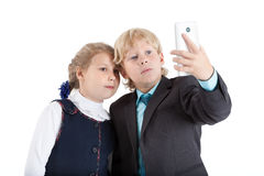 Cute schoolchildren making selfie picture with smartphone together, isolated white background Stock Photography