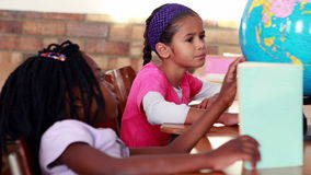 Cute schoolchildren reading and looking at globe in their classroom. In elementary school stock footage