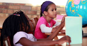 Cute schoolchildren reading and looking at globe in their classroom. In elementary school stock video footage