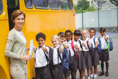 Cute schoolchildren waiting to get on school bus Royalty Free Stock Image