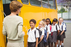 Cute schoolchildren waiting to get on school bus Stock Photos
