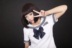 Cute schoolgirl. Cute Asian schoolgirl in uniform posing on dark Royalty Free Stock Photography