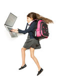 Cute schoolgirl with backpack using laptop while walking Stock Images