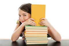 Cute Schoolgirl behind a stack of books Royalty Free Stock Photography