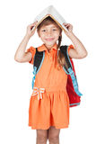 Cute schoolgirl with book on his head and a red backpack on her Stock Photo